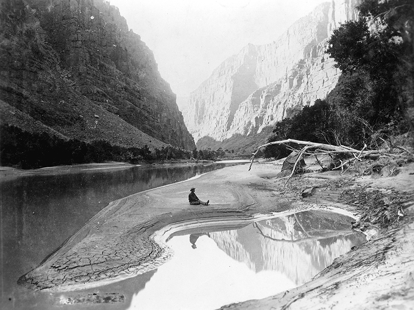 Black-and-white photo of a man sitting on a sand bank in a deep river canyon