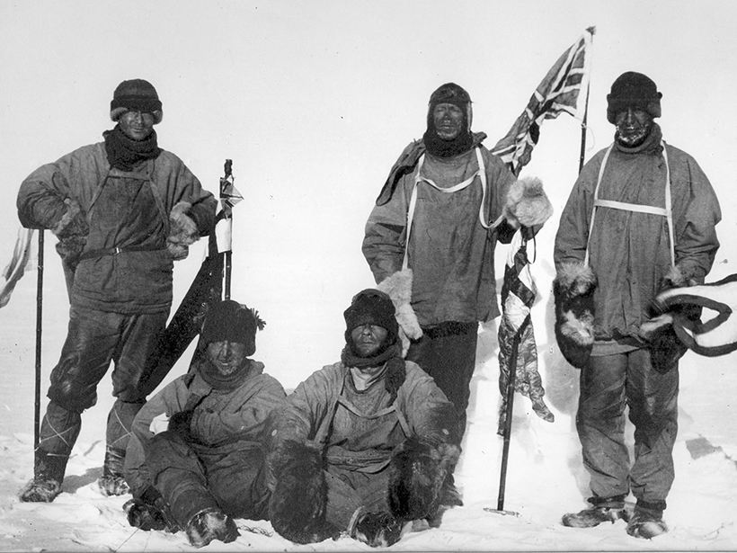 Black-and-white photo of unsmiling white explorers at the South Pole
