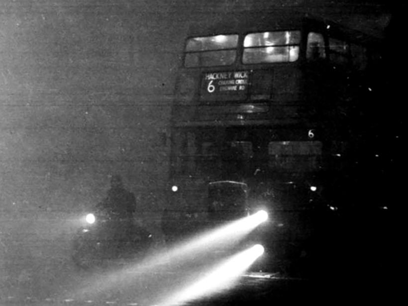 Black-and-white photo of a motorcycle and double-decker bus in thick fog