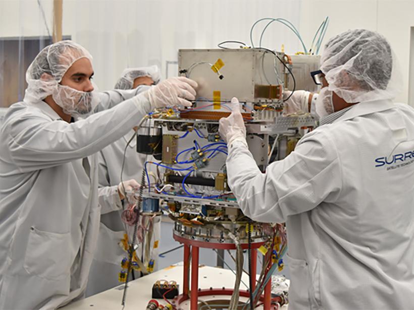 People in lab safety gear adjust a machine