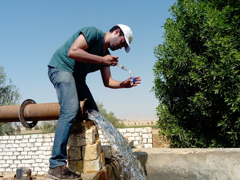 Man collects water from a pipe to put in a test tube.
