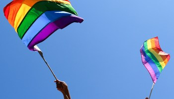 Caucasian hands wave rainbow flags in front of blue sky