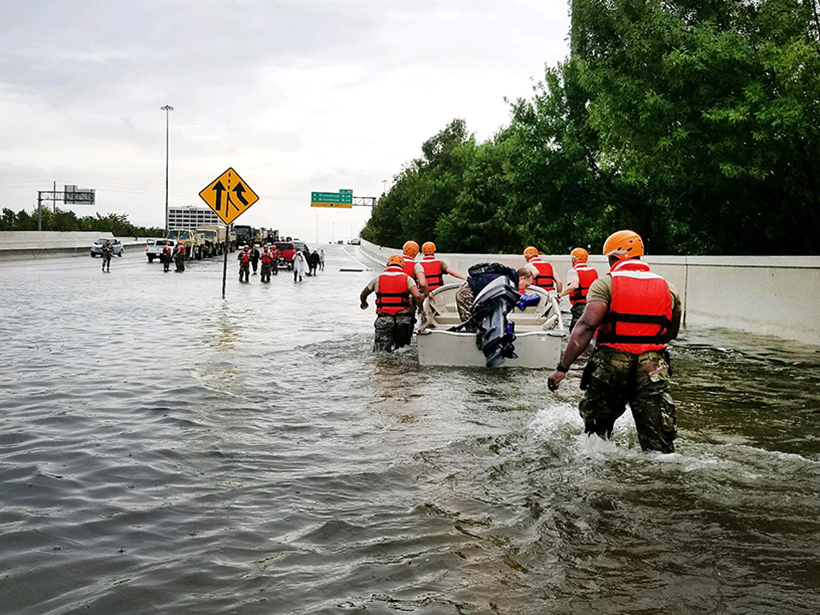 National Guard rescue man in boat on flooded street