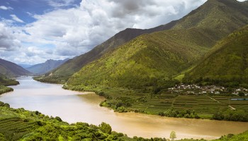 Photo of the Yangtze River flowing through a valley lined with greenery and agricultural terraces in China
