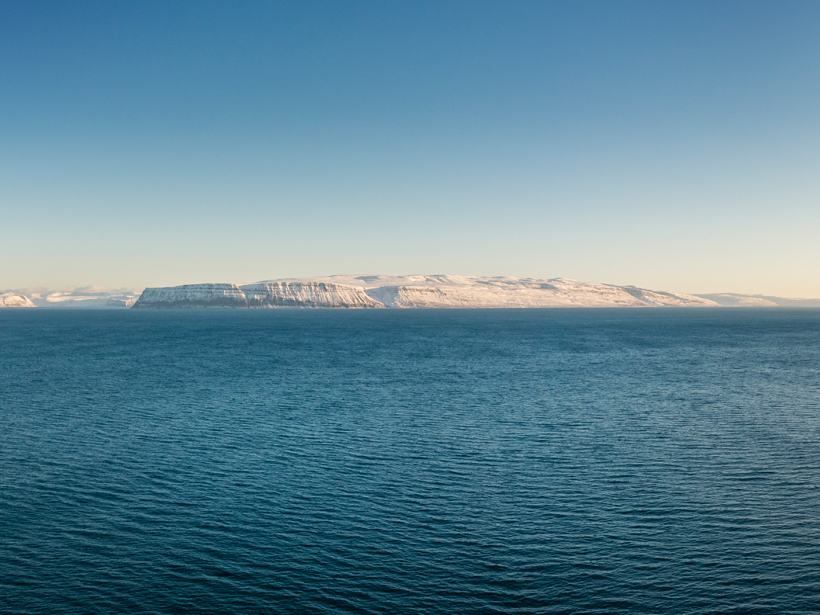 A stretch of the North Atlantic Ocean with the snow-covered shoreline of western Iceland in the background