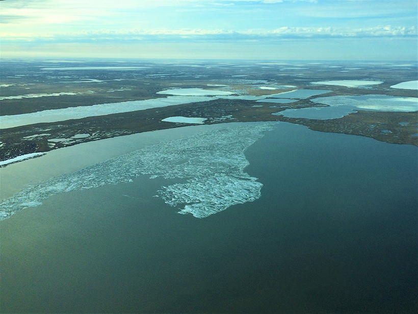 Aerial view over the Alaskan tundra showing patches of snow, ice, and bare land