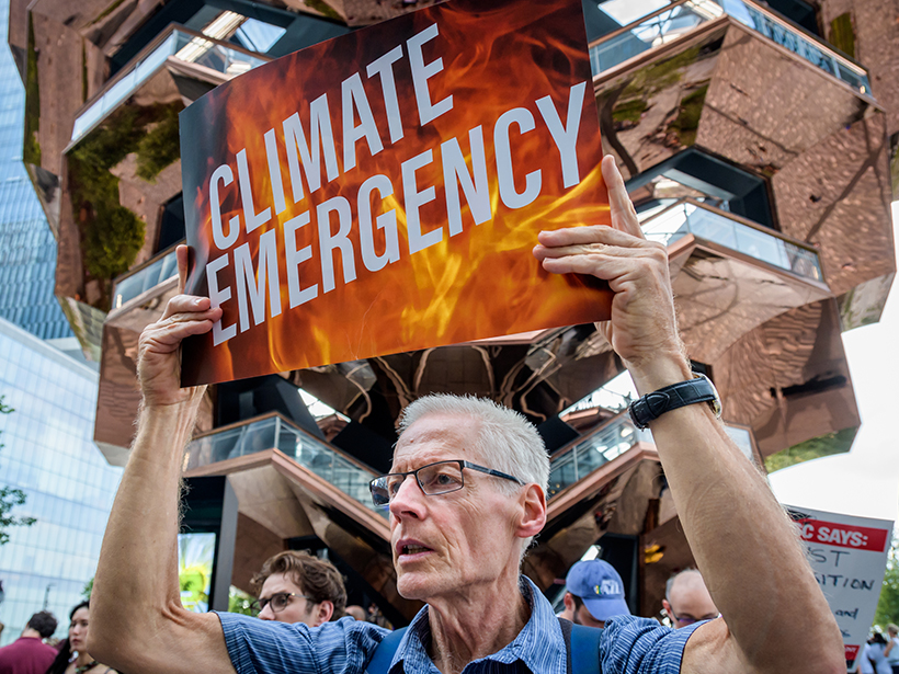"""White man holds sign outside CNN climate town hall reading """"Climate Emergency"""""""