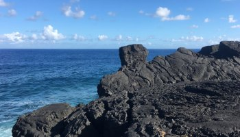 A landscape of dark volcanic rocks forefronts a beautiful blue ocean.