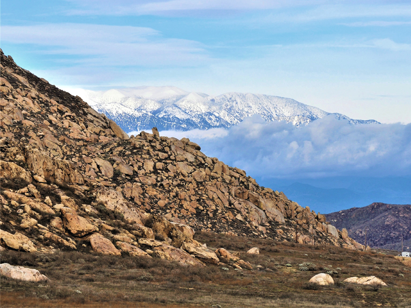 An image of snowcapped mountains in the background with beige, eroded material from those mountains in the foreground