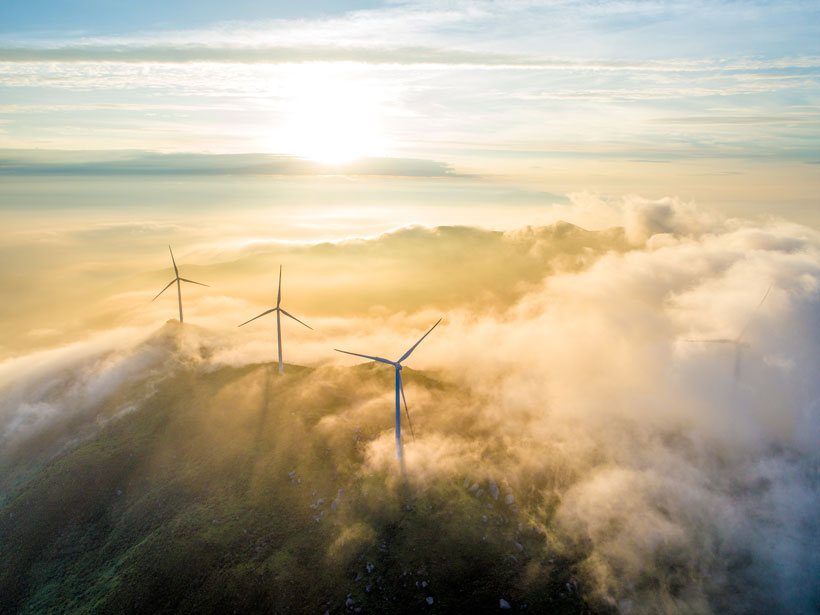 Aerial photo of large wind turbines on a cloudy mountaintop