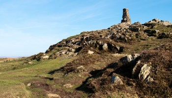 A small stone tower stand atop a small rocky hill.