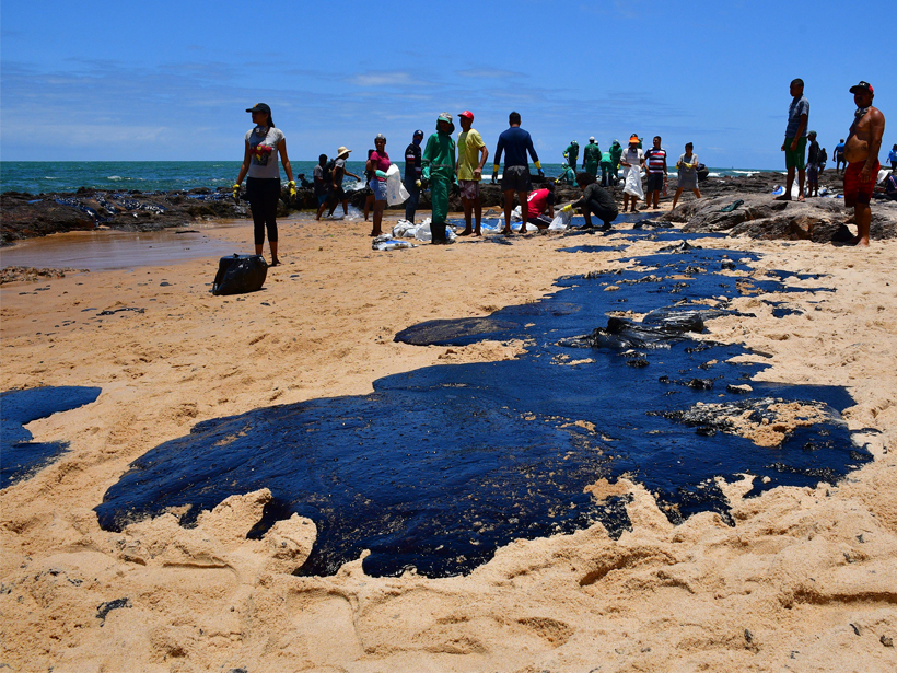 A puddle of oil lays on sand on a beach