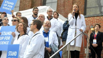 Earth and space scientists in white lab coats speak at a rally on the steps of a building.