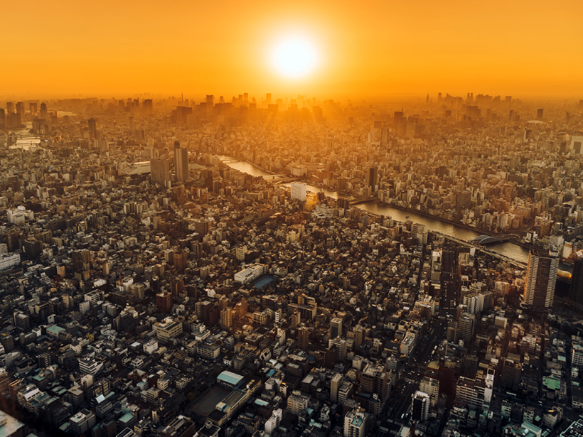 Image of orange sun above hazy Tokyo cityscape