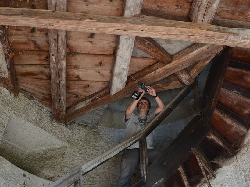 A man uses a tool to extract a tiny sample of a construction timber in a wooden roof.