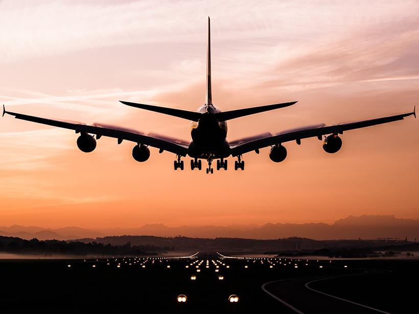 A plane lands at sunset
