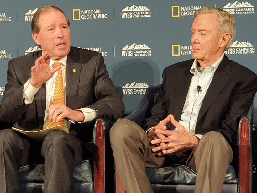 Sen. Tom Udall and former secretary of the interior Bruce Babbitt sit on a dais with National Geographic logos everywhere