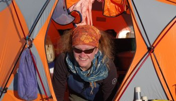 Glaciologist Erin Pettit, in a bandana and sunglasses, smiles from the door of a tent in Antarctica.