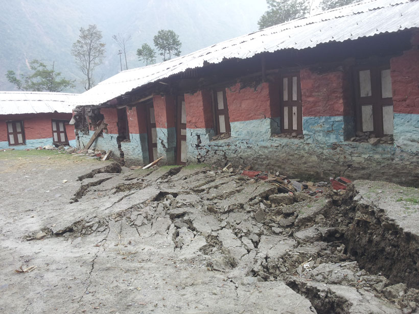 Large earthen rupture foregrounds a brightly colored school building damaged by an earthquake.