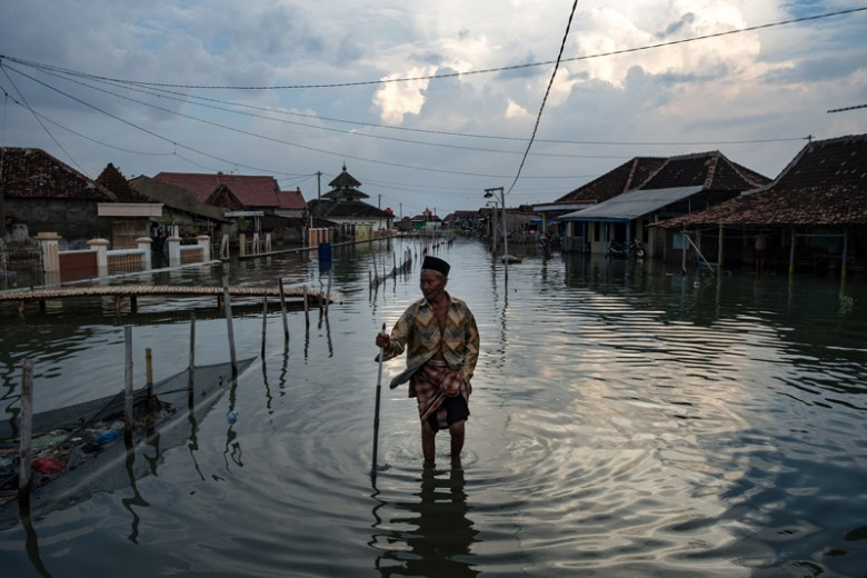 A man wades through calf-deep water on a residential street in Java, Indonesia.