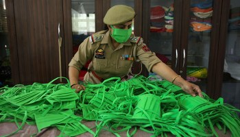 An officer checks the quality as police personnel make face masks and personal protective gear amid COVID-19 outbreak in Jammu, India.