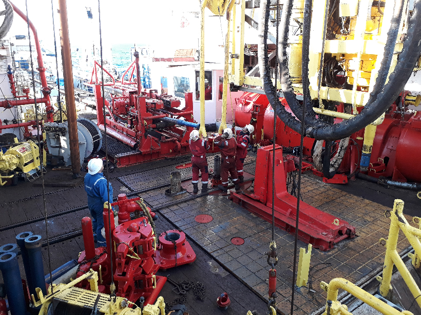 Drillers in hardhats work on the rig floor of a research vessel.