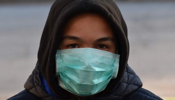 Young man in a hoodie wearing a surgical mask outdoors