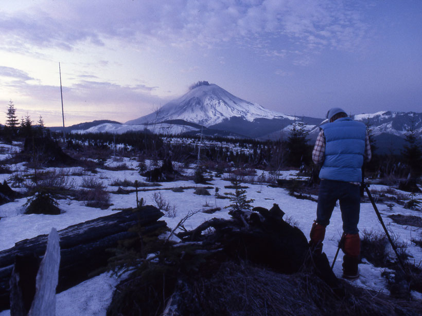 A scientist surveys a smoking Mount St. Helens in a wintry landscape.