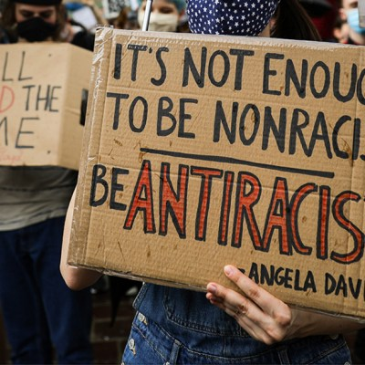 Handwritten cardboard signs from a Black Lives Matter protest in Poland, centered on a quote from Angela Davis about antiracism.