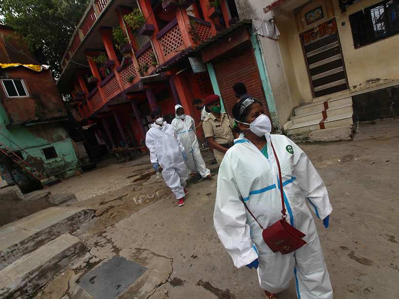 Health care workers in masks and hazmat suits walk through a residential area in India.