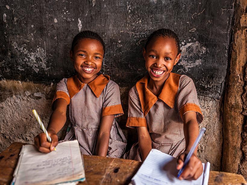 Two beaming schoolgirls sit at a desk in Nairobi, Kenya.