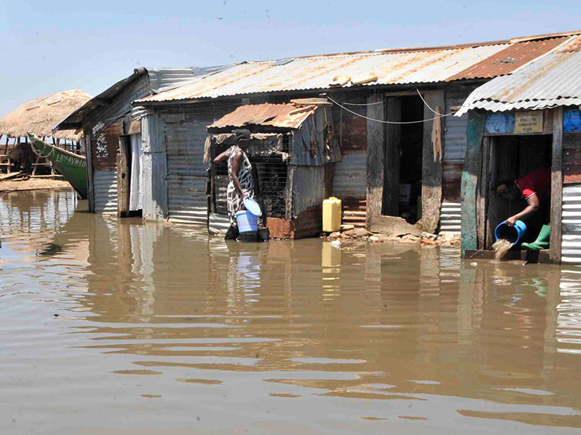 High water enters metal structures on Lake Victoria, with three people carrying buckets