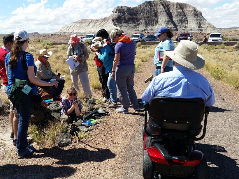Group of men and women, some with walking sticks and one in a wheelchair, collects data in a field near a mountain