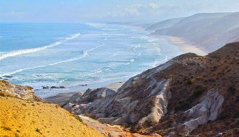 A view along the Atlantic coastline of South Africa showing hillslopes descending to the beach and ocean