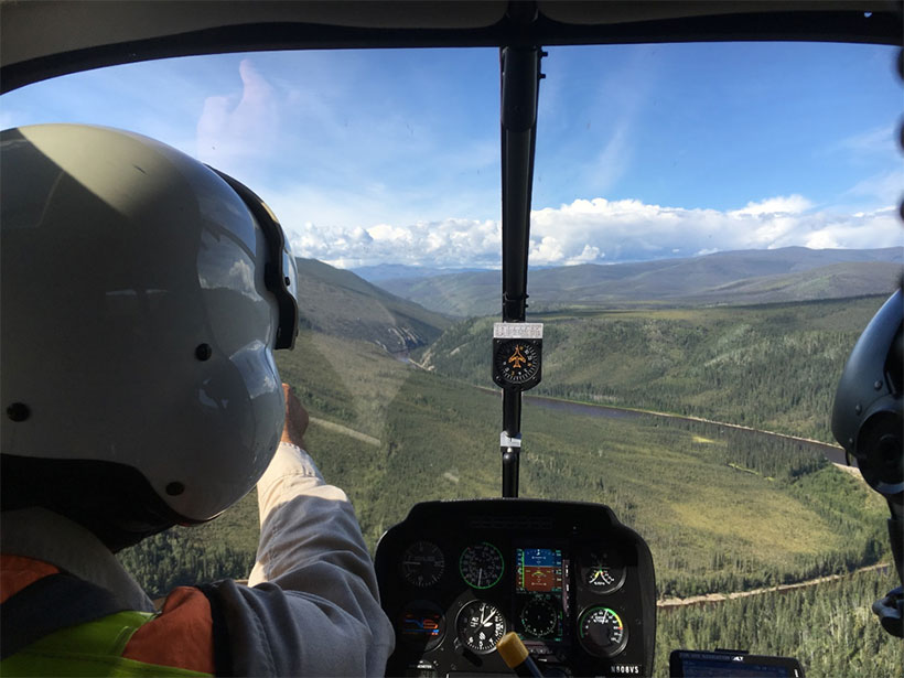 View looking out a helicopter cockpit over remote eastern Alaska landscape