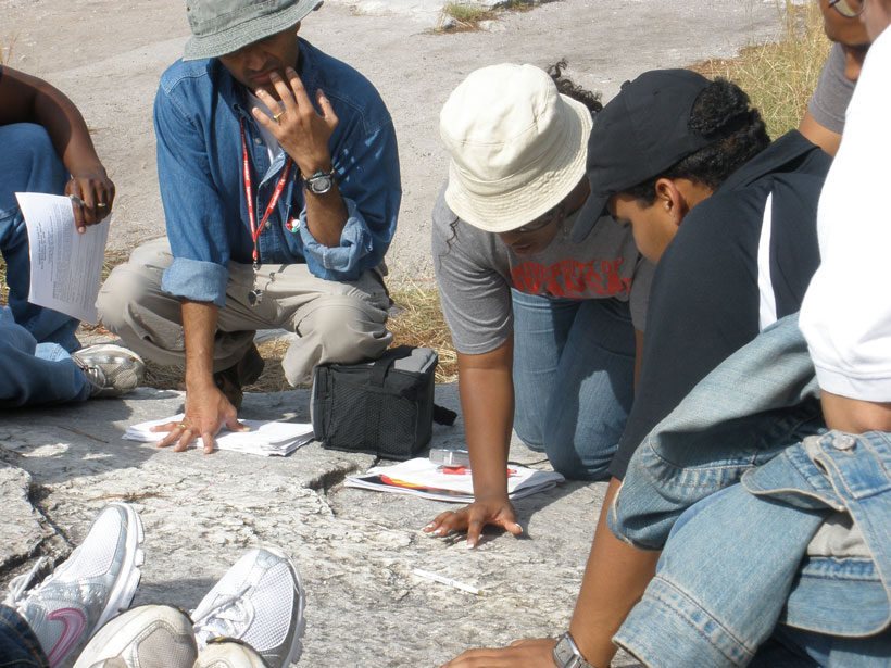 A group of students crouch over a flat rock formation outdoors