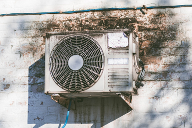 Photograph of an air conditioning unit on the side of a building