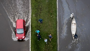 Aerial view of a boat and a car on a flooded street in La Plata, Argentina.