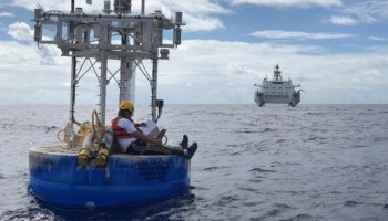 A researcher checks a carbon sensor manual on a floating research buoy while a research ship waits in the distance