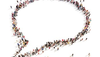 Stock image depicting many people from above standing in the shape of a speech bubble