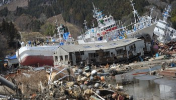 Deformed buildings, beached boats, and debris litter a coastline in Japan.