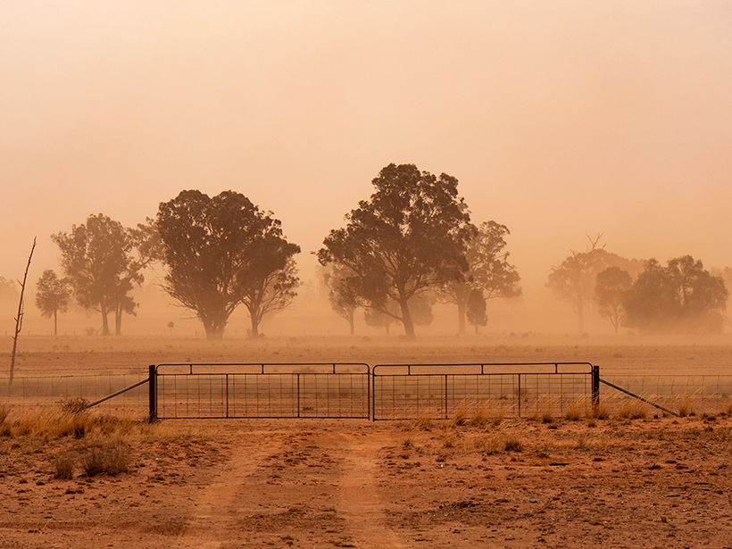 A metal gate across a rural road during a dust storm in a dry landscape