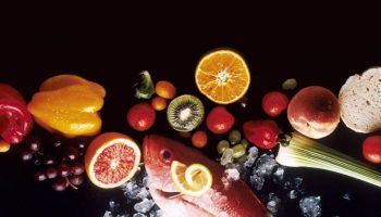 A black table holding assorted foods, including orange and red peppers, red grapes, oranges, kiwi, tomatoes, brussels sprouts, peaches, celery, fish, and bread