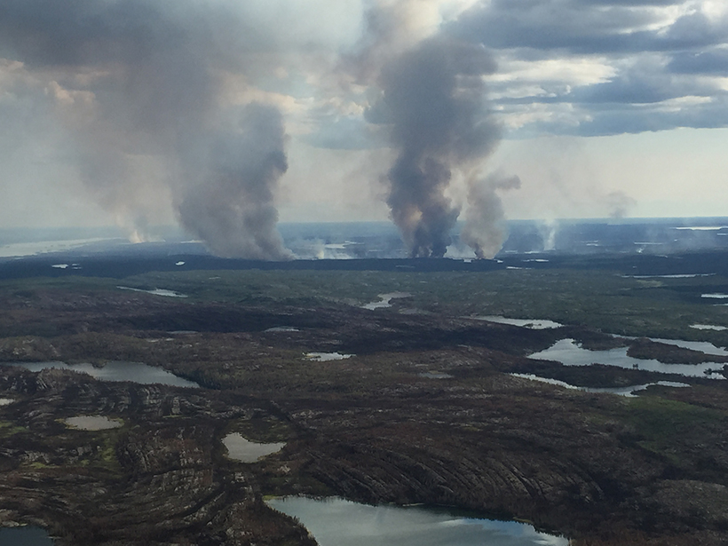Smoke rises from a singed landscape, meeting the clouds above a swath of boreal forest punctuated by lakes.