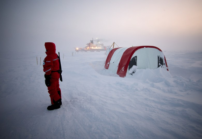 A person stands watch outside a tent on sea ice