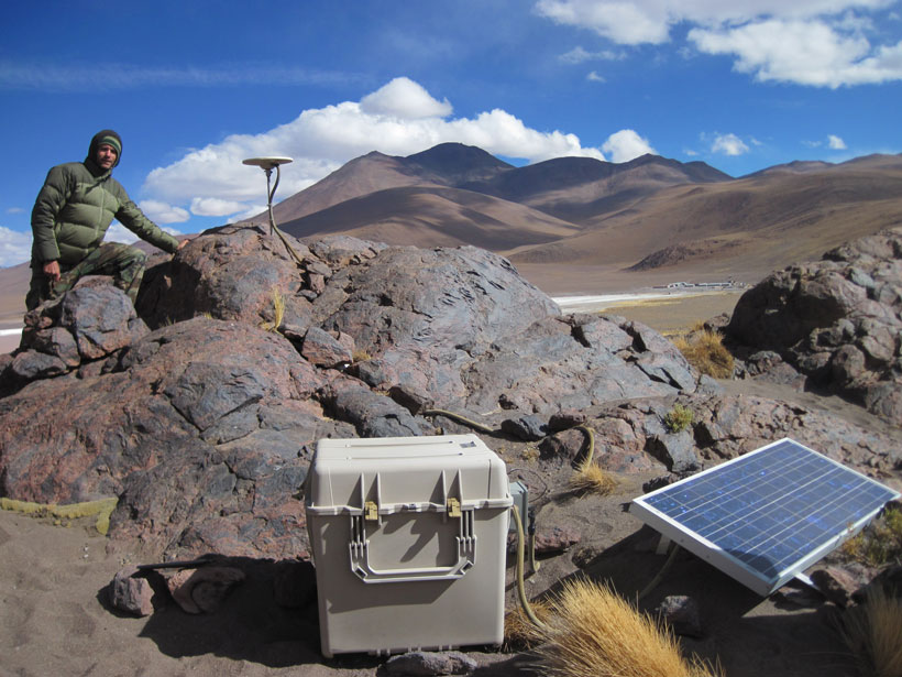 A researcher checks a GPS ground motion sensor amid the rocky, barren landscape of the Altiplano-Puna Plateau in the southern Bolivian Andes