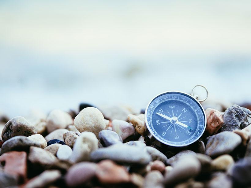 A handheld compass sits amid rocks on a beach