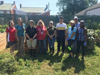 Young men and women stand in front of raised beds at an urban gardening site.