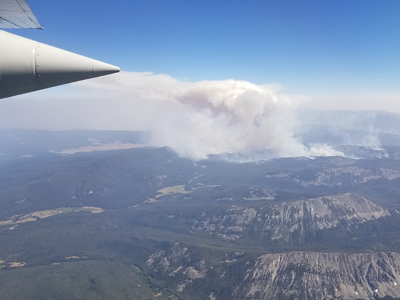 Aerial view of a wildfire smoke plume rising from a mountainous landscape