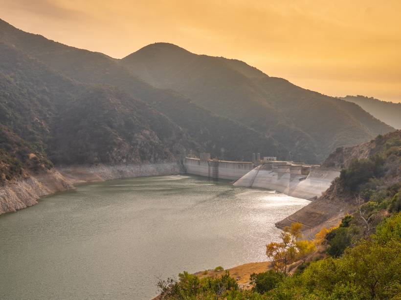 View from upslope of a water reservoir situated among mountains